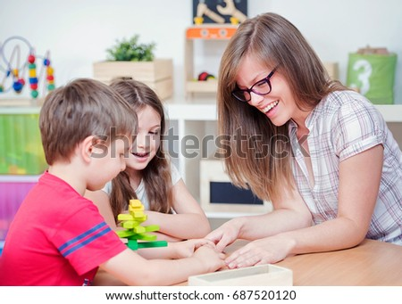 Mother and Kids Playing with Wooden Toy Building Blocks