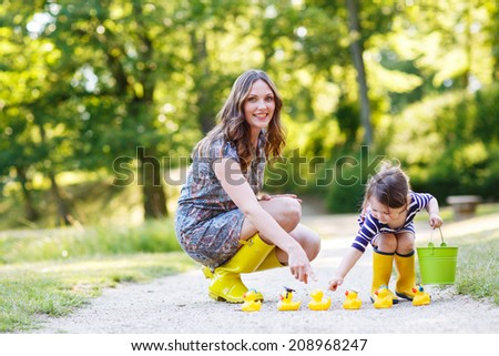 Mother and little adorable daughter in yellow rubber boots, family look, playing with duck toys in summer park