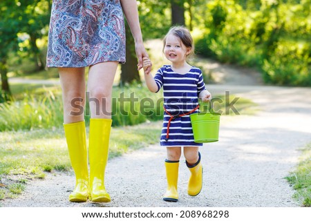 Mother and little adorable toddler child in yellow rubber boots, family look, in summer park - stock photo