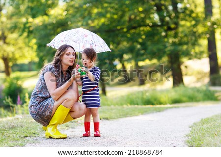 Mother and little adorable toddler daughter in yellow rubber boots, family look, playing with frog toy in summer park - stock photo
