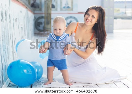 Mother and little baby boy with balloons outdoors
