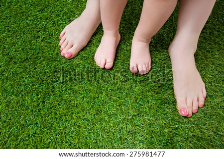 Mother and little baby legs standing  on grass