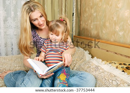Mother and little blond girl reading - stock photo