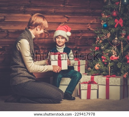 Mother and lIttle boy with gift box under christmas tree in wooden house interior  - stock photo