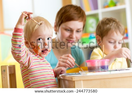 mother and little boys messily playing with paints at home - stock photo