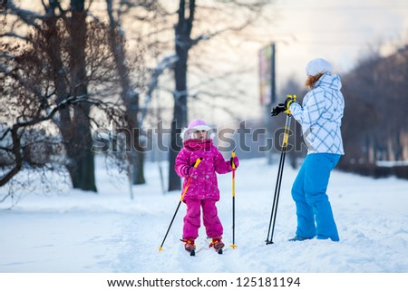 Mother and little child on ski in city park - stock photo
