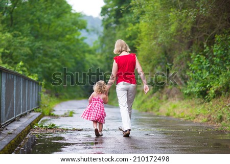 Mother and little curly toddler girl walking together in a park on a wet summer day after rain, view from the back