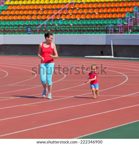 Mother and little daughter are engaged in running in the stadium. family doing fitness at the stadium - stock photo