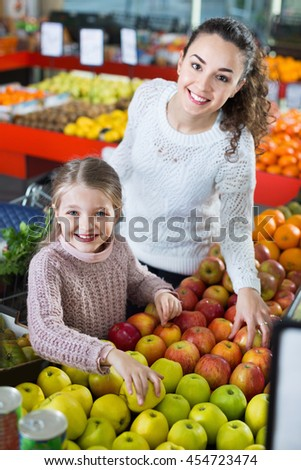 Mother and little daughter choosing seasonal fruits in grocery