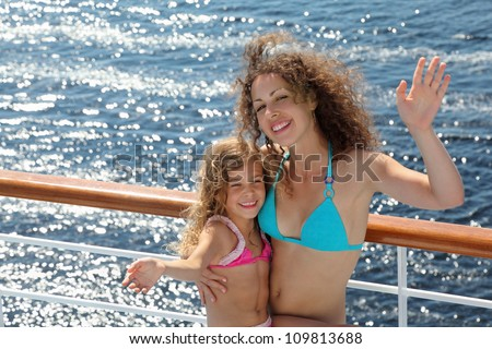 Mother and little daughter dressed in swimsuits wave their hands on deck of ship
