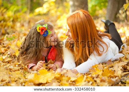 Mother and little daughter having fun and talking in the autumn park.