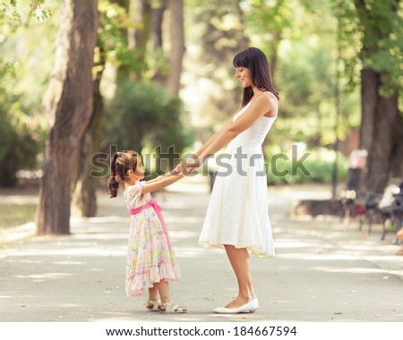 Mother and little daughter having fun in a park on a nice sunny day. - stock photo