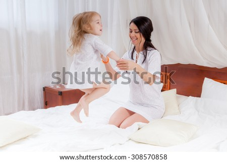 mother and little daughter jumping on bed - stock photo