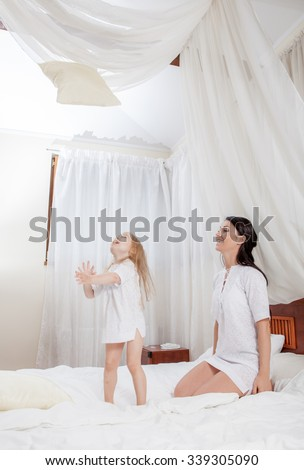 mother and little daughter on bed - stock photo