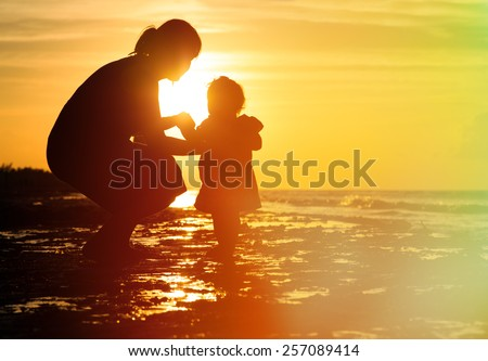 mother and little daughter on sunset tropical beach - stock photo