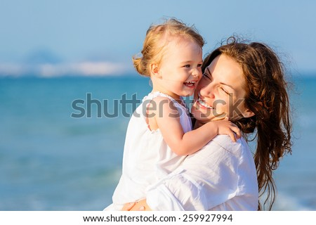 Mother and little daughter on the beach - stock photo