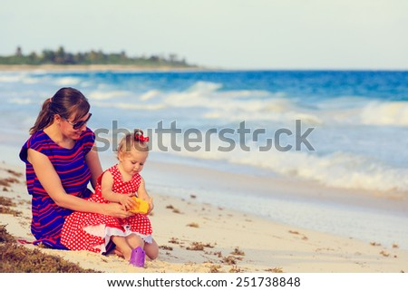 mother and little daughter on tropical sand beach - stock photo