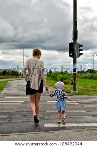 Mother and little daughter on zebra crossing - stock photo