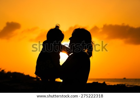 mother and little daughter play at sunset beach - stock photo