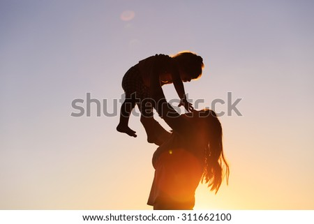 mother and little daughter play at sunset sky - stock photo