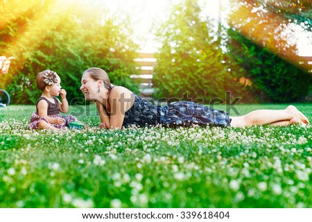 Mother and little daughter sit on the grass in a park at a picnic. - stock photo