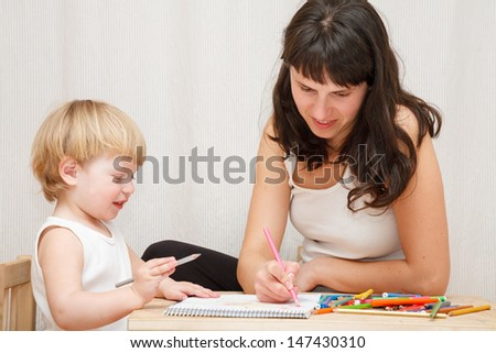 mother and little daughter sitting at the table drawing together at home