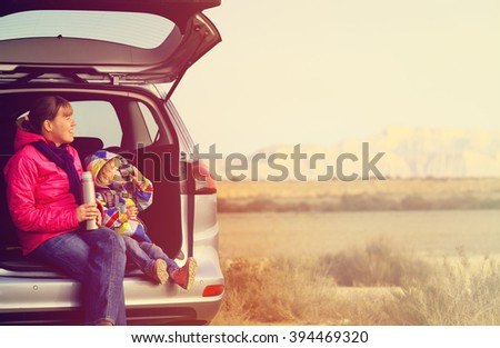 mother and little daughter travel by car in mountains - stock photo
