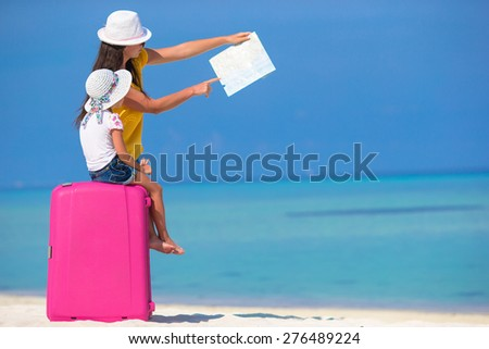 Mother and little daughter with big bag on white beach - stock photo