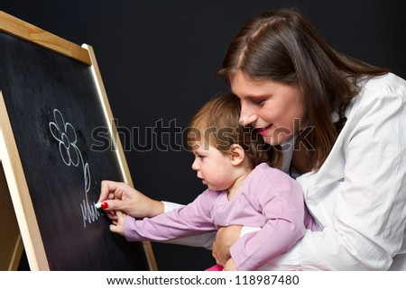 Mother and little daughter writing on a blackboard - stock photo
