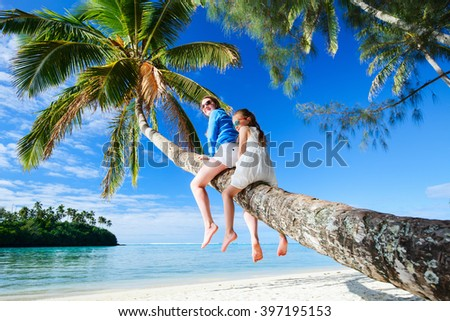 Mother and little girl at tropical beach sitting on palm tree during summer vacation on exotic island in South Pacific