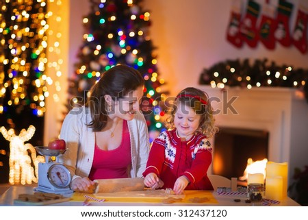 Mother and little girl baking Christmas pastry. Children bake gingerbread. Toddler child preparing cookie for family dinner on Xmas eve. Decorated kitchen or dining room with fireplace, tree, candles. - stock photo