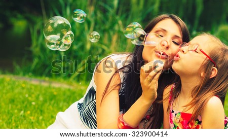 Mother and little girl daughter child blowing soap bubbles outdoor. Parent and kid having fun in park. Happy and carefree childhood. Good family relations. - stock photo