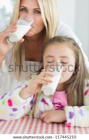 Mother and little girl drinking milk at the kitchen at breakfast - stock photo