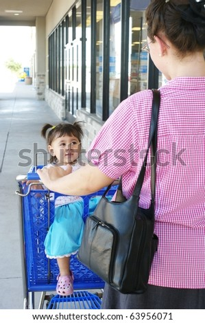 Mother and little girl shopping, outdoors with shopping cart