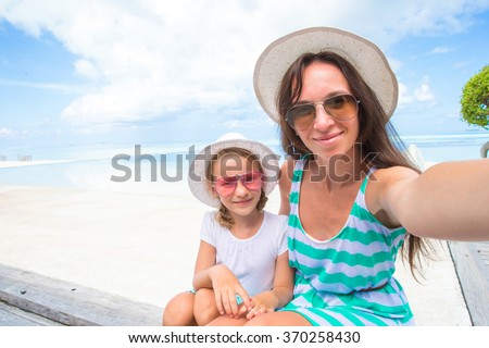 Mother and little girl taking self portrait at tropical vacation - stock photo