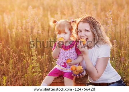 mother and little girl with peach outdoor - stock photo