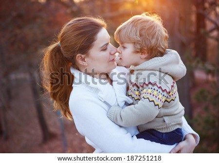 Mother and little son in park or forest, outdoors. Hugging and having fun together. - stock photo