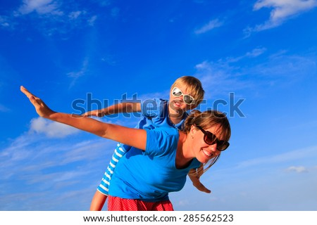 Mother and little son playing airplane on blue summer sky