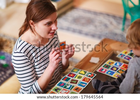 Mother and little son playing together education card game for children. - stock photo
