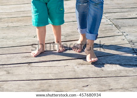 Mother and little son walking barefoot on pier. Cropped image on their legs.