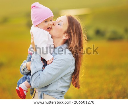 Mother and lovely daughter at sunny field. Happy family concept.