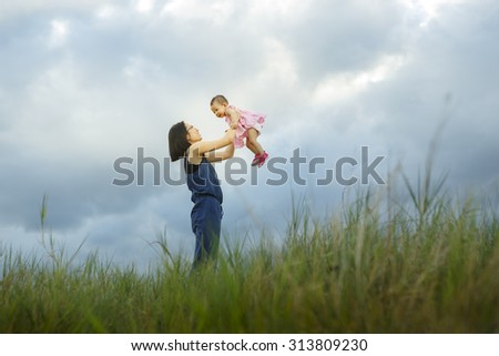Mother and new born playing on the garden at the sunset time. Concept of friendly family - Vibrant color effect - stock photo