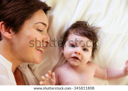 Mother and newborn son on the bed at home