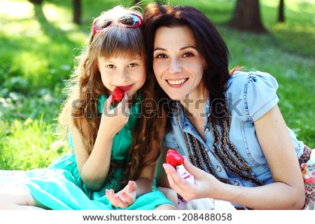mother and preteen daughter summer portrait with strawberries in the green beautiful park - stock photo