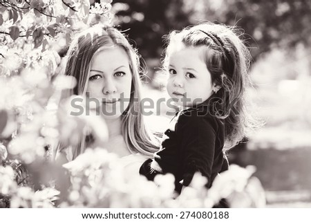 mother and pretty todd;er girl in blossom garden - stock photo