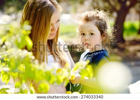 mother and pretty toddler girl in blossom garden - stock photo