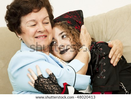 Mother and rebellious goth daughter hugging each other.