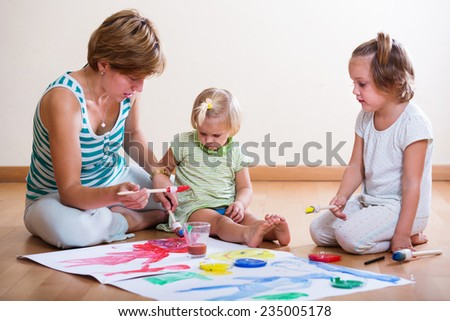 Mother and siblings painting with paint on floor indoor