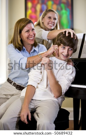 Mother and sister having fun teasing teenage boy at home - stock photo