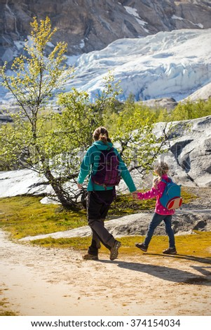 mother and sisters hiking on the lake with  mountains and the glacier Nigardsbreen at the background